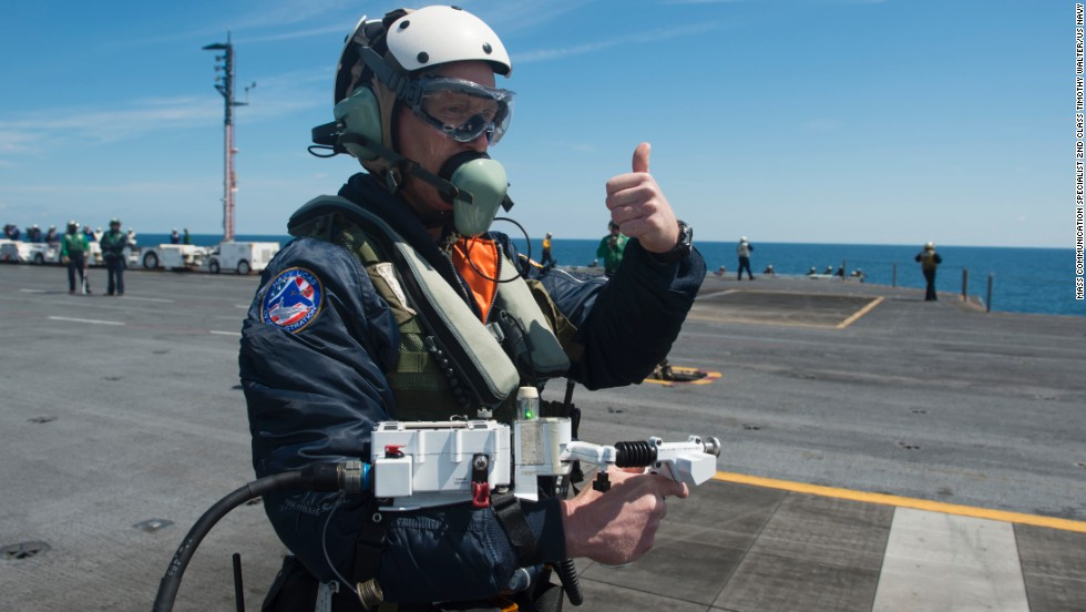 Dave Lorenz, a deck operator for Northrop Grumman, has control of the drone as he moves it via an arm-mounted controller.