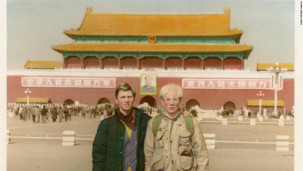 Christopher Makos (L) and Andy Warhol (R) had their picture taken in front of Tiananmen Square by one of the photographers hanging around the area.  Back in the U.S., they received the hand-colored photo in the mail a few months later.