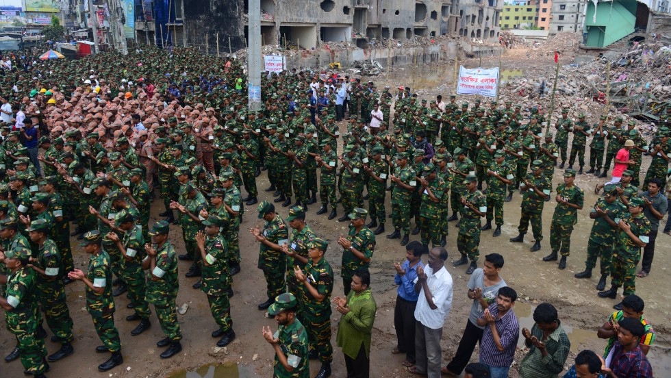 "Members of the Bangladesh army pray at the site of the collapsed Rana Plaza in Savar near Dhaka on Tuesday, May 14. The army-led effort to search for bodies has ended nearly three weeks after the nine-story building collapsed. <a href=""http://www.cnn.com/2013/05/14/world/asia/bangladesh-building-collapse-aftermath/?hpt=hp_t2"">The final death toll stands at 1,127</a>."
