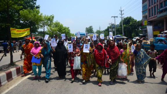 Marching Bangladeshis hold up portraits of relatives missing in the Rana Plaza building collapse on Tuesday, May 14. They