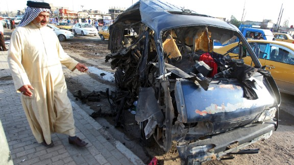 An Iraqi man looks at the remains of a vehicle at the scene of a car bomb explosion in Baghdad