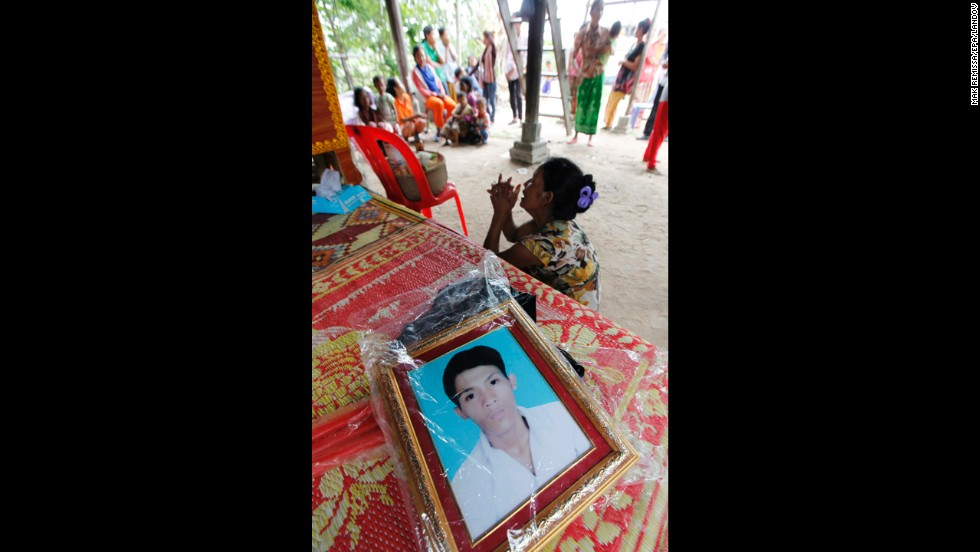 Kim Leap grieves next to a portrait of her son Rim Saroeun. Saroun, 22, was one of eight family members who worked at the factory, a relative said.