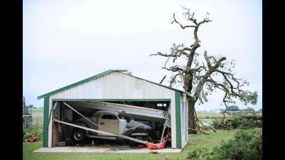 An antique car sits in a collapsed garage on May 16 in Granbury.