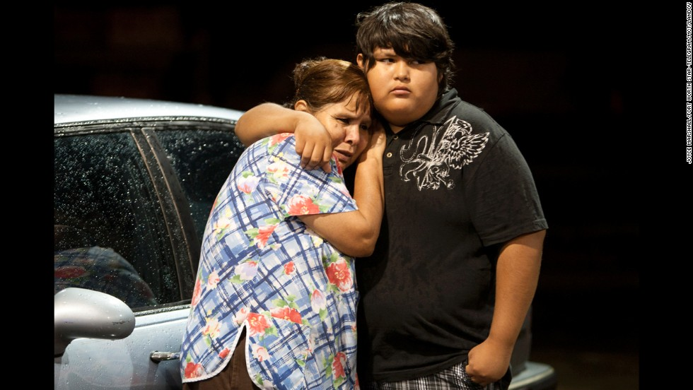 Eva Zapata, left, waits with a relative, Dario Segura, on May 15 for news of her children, who live in the Granbury neighborhood of Rancho Brazos. Six of the storm victims came from that subdivision, the Hood County sheriff said.