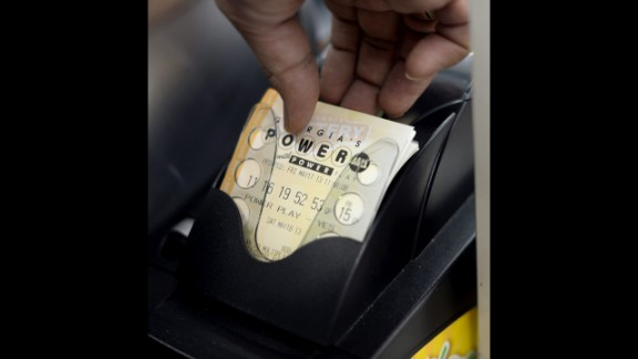 A lottery retailer pulls a Powerball ticket from the printer in Decatur on May 17. A single ticket costs $2.