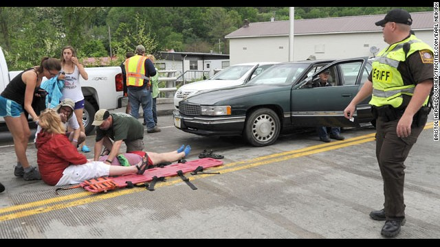 Victims get help and a man who appears to be the driver sits in the car.