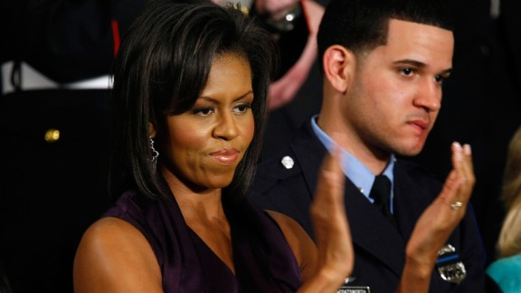 Officer Richard DeCoatsworth stands beside Michelle Obama during a presidential speech in 2009.