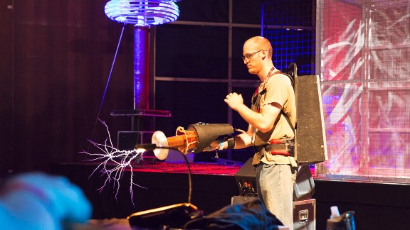 A man demonstrates the ArcAttack's portable Tesla coil in front of Tesla coils in the Maker Faire Fiesta Hall.