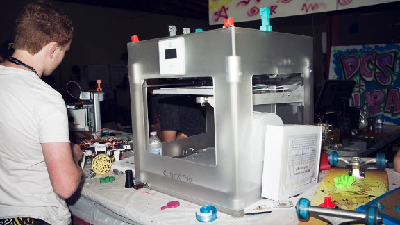 3-D printers were everywhere at the 2013 Maker Faire. This $3,999 CubeX Trio is printing a small plastic guitar.