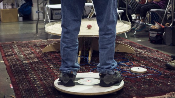 A man guides a ball through a maze with his body weight on an Arduino-powered board as part of the Big Ball Maze Game.