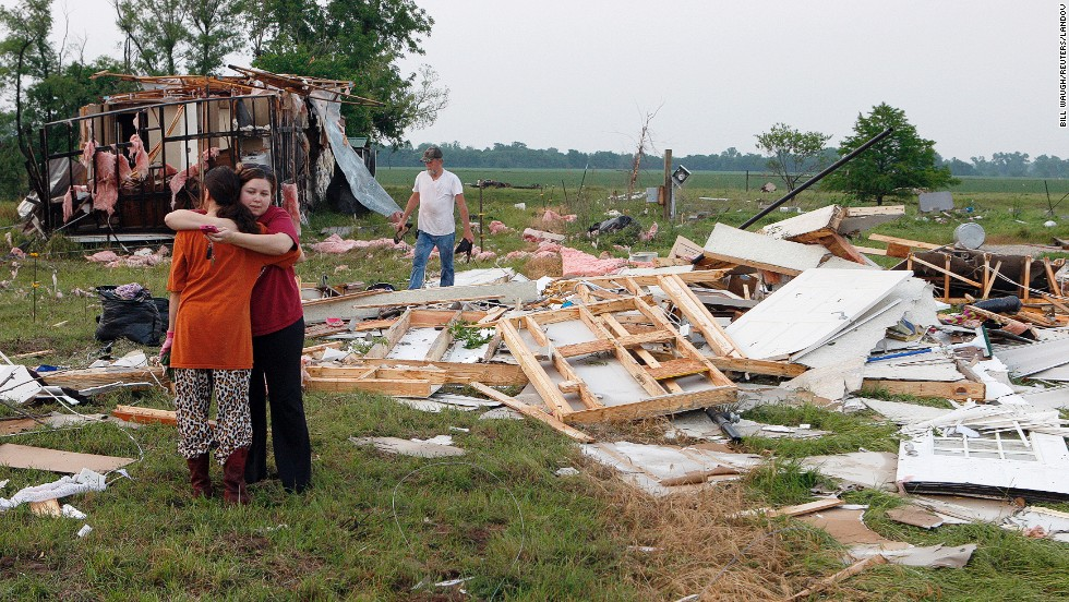 Shawnee residents embrace on May 20 as they search through the remains of their home.
