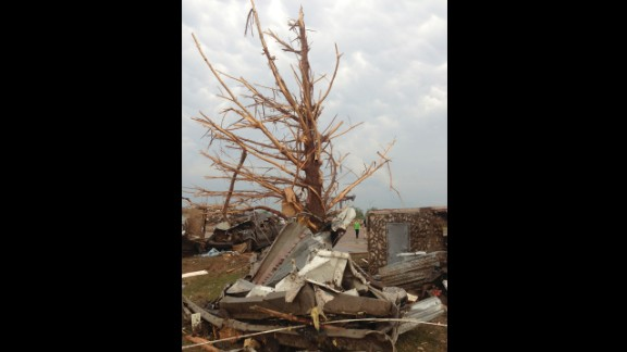A shredded tree stands amid debris in the aftermath of the storm in Moore on May 20.