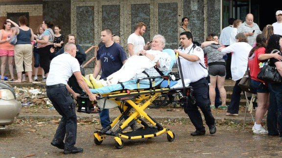 A man is taken away from the IMAX Theater in Moore that was used as a triage center on May 20.