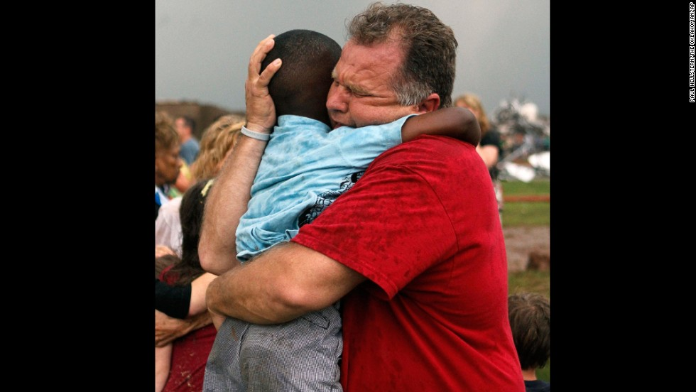 "Jim Routon hugs his neighbor, 7-year-old Hezekiah, after the tornado strikes on May 20. An earlier version of this caption incorrectly stated that Routon was Hezekiah's teacher. <a href=""http://outfront.blogs.cnn.com/2013/05/21/neighbors-comfort-boy-in-tornado-aftermath/"">See an interview with the pair.<strong></a> </strong>"