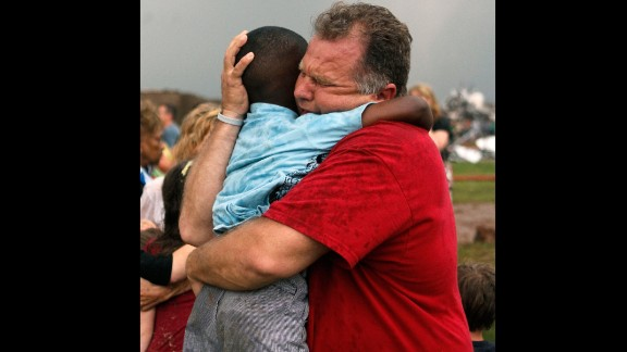 Jim Routon hugs his neighbor, 7-year-old Hezekiah, after the tornado strikes on May 20. An earlier version of this caption incorrectly stated that Routon was Hezekiah