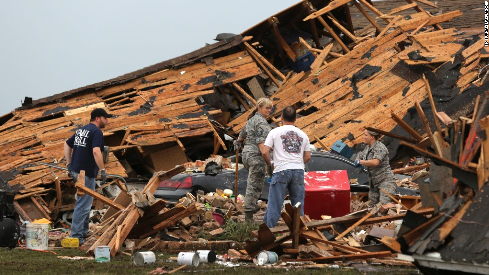 People sort through a leveled home in Moore on May 21.