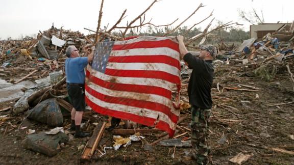 Men tie an American flag on debris in a neighborhood off Telephone Road in Moore on May 20.