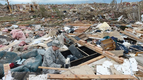 Air Force Airman First Class Justin Acord sifts through the rubble of his father-in-law
