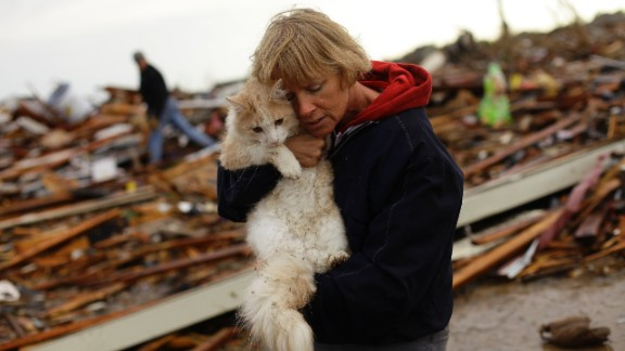 June Simson embraces her cat Sammi after she found him standing among the rubble of her destroyed home in Moore on May 21.