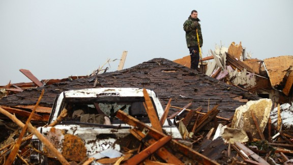A man stands on the roof of a destroyed home in Moore on May 21.