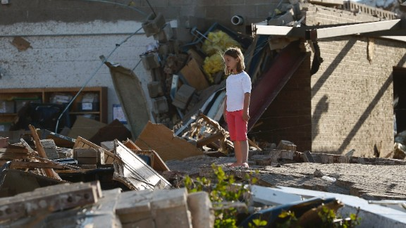 A young girl stands among the rubble outside Briarwood Elementary School on May 21.