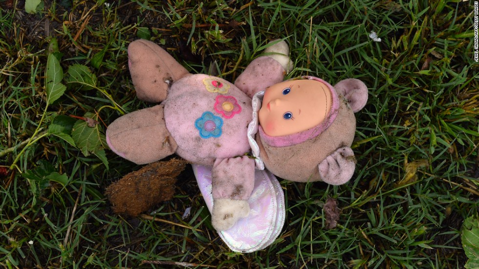 A doll covered in dirt is among the rubble scattered throughout a neighborhood in Moore on May 21.