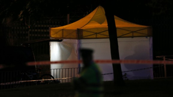 A police officer guards a tent that's been set up at the crime scene as investigations continue late May 22.