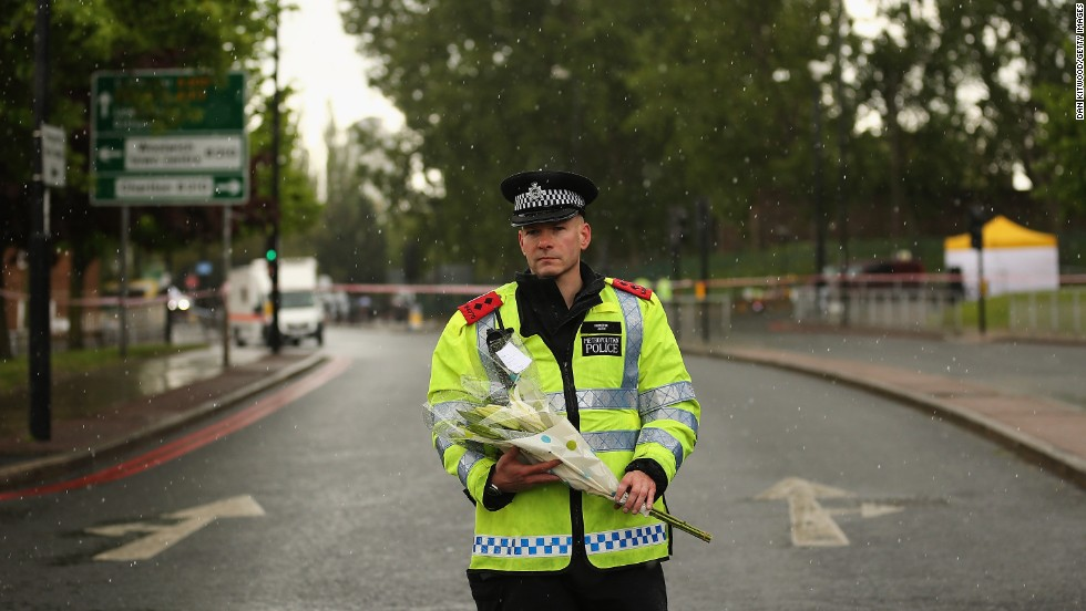 A police officer stands with flowers in a storm on Thursday, May 23, close to the crime scene in front of Woolwich Barracks in southeast London.