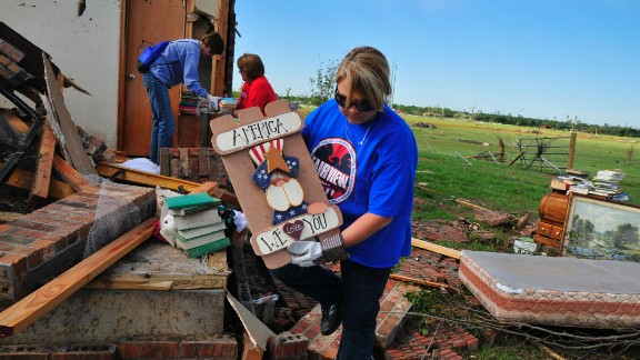 Lisa Brown helps her former colleague Kay Taylor pull belongings from the wreckage of her home. Taylor, a former PE teacher and school counselor, was most concerned about finding her collections of pennies, gumball machines and ladybug figures.