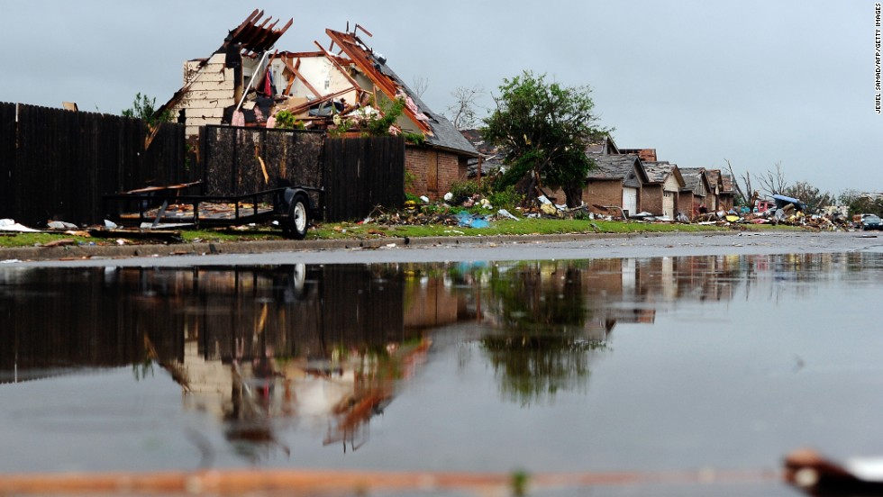 Rubble lines a wet street in a tornado-devastated neighborhood in Moore, Oklahoma, on Thursday, May 23. Severe thunderstorms barreled through this Oklahoma City suburb at dawn Thursday, complicating cleanup efforts three days after a powerful tornado ripped through the area.