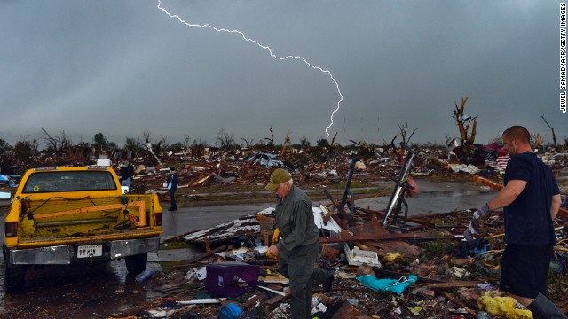 Lightning strikes during a thunder storm as people search for salvagable items at their devastated home on May 23, in Moore, Oklahoma.