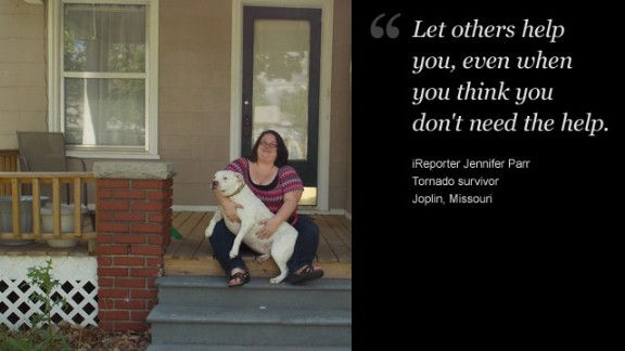 Jennifer Parr and her dog, Lulu, sit in front of their new home. Parr's house was a complete loss after the Joplin tornado.