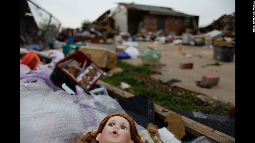 Debris is scattered across a driveway on May 23. Severe thunderstorms barreled through this Oklahoma City suburb at dawn Thursday, complicating cleanup efforts.
