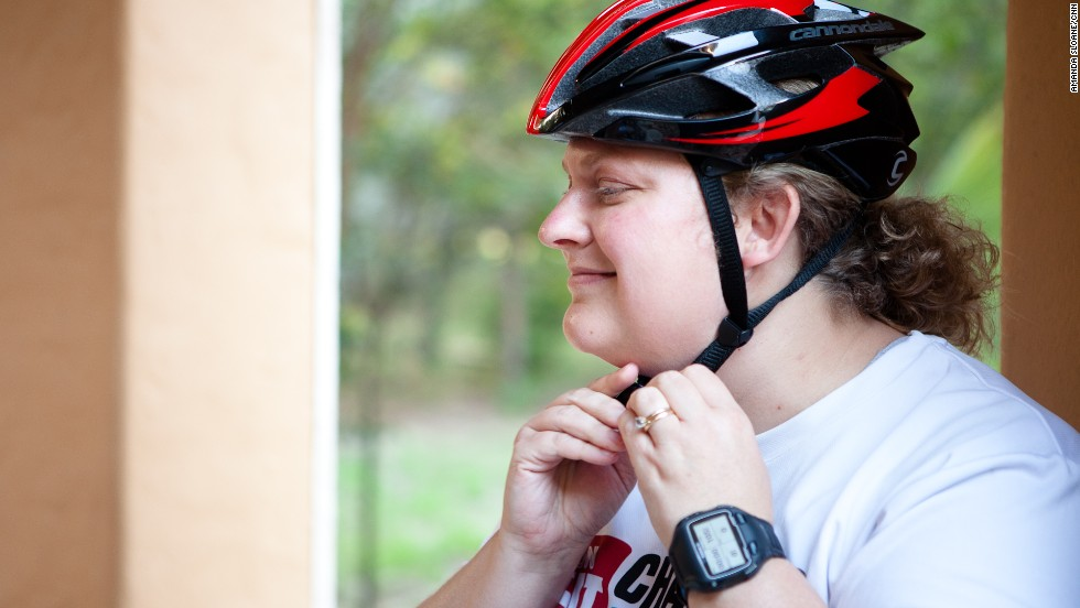 Tabitha McMahon straps on her helmet as she prepares for one of the group's training rides.