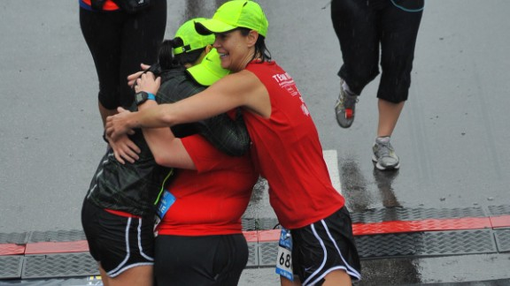 Anje and Darbi hug Annette Miller tightly at the finish line of the half marathon.