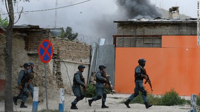 Afghan policemen run to the site of a clash between in Kabul, Afghanistan, on May 24, 2013.