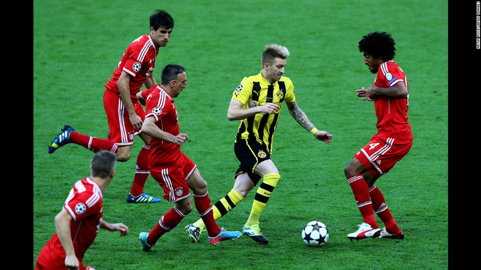 Marco Reus of Borussia Dortmund, center, drives to the goal against Dante, right, of Bayern Munich.