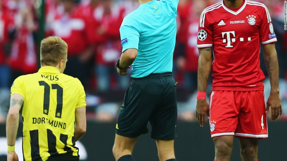 Dante, right, of Bayern Munich is given a yellow card after being called on a foul against a Borussia Dortmund player.