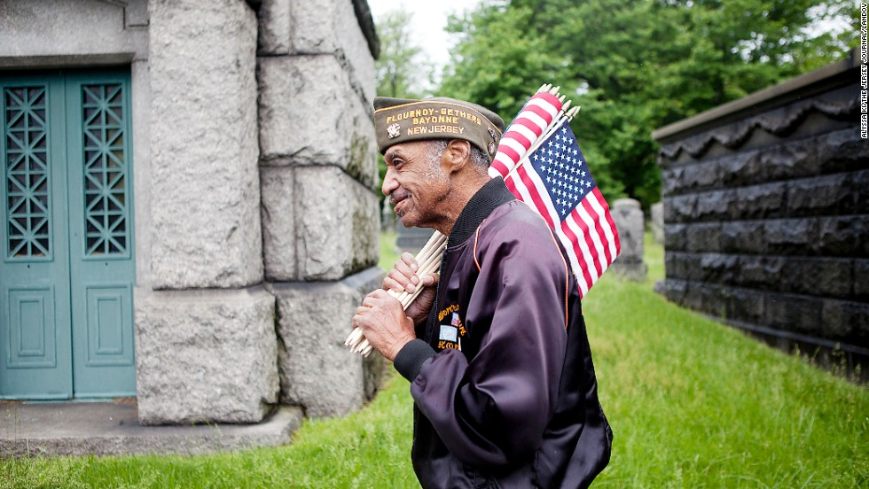 James Venable, 82, carries flags to place on veterans' graves at Bayview Cemetery in Jersey City, New Jersey, on May 25.