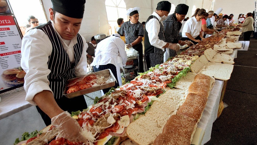 Cooks make a 46-metre-long 'torta' (Mexican sandwich) during the annual 'Torta Festival' in Mexico City, on July 31, 2009. More than 200 people helped to make the giant sandwich, which included meat, chicken, avocado, mole (Mexican spicy sauce), turkey, tomatoes, beans, ham and different types of cheese in an attempt to break the record for the longest 'torta'.