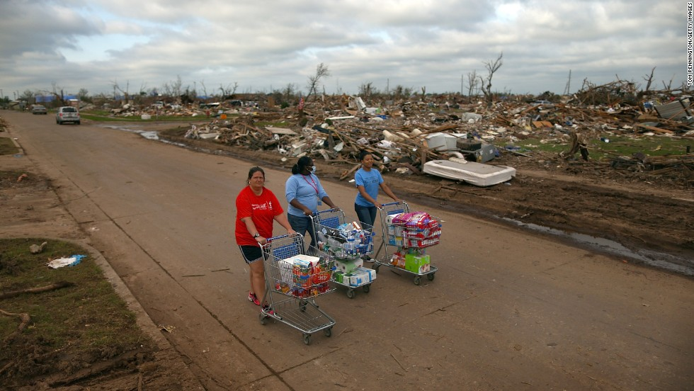 Left to right, Jaqi Castro, Angelica Morris-Smith and Cetoria Petties walk through a tornado ravaged neighborhood handing out supplies to residents and fellow volunteers on May 27.