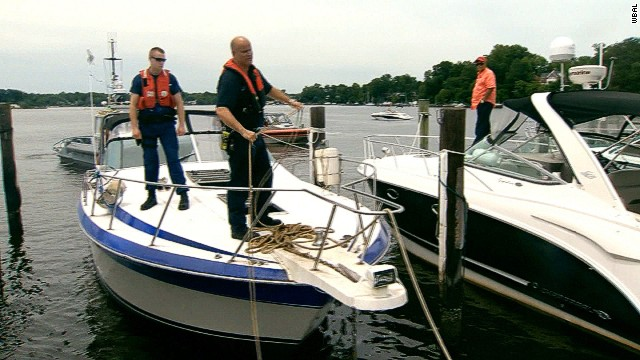 Officers dock a boat that exploded, injuring six people at the Oak Grove Marina, near Edgewater, Maryland, on Monday..