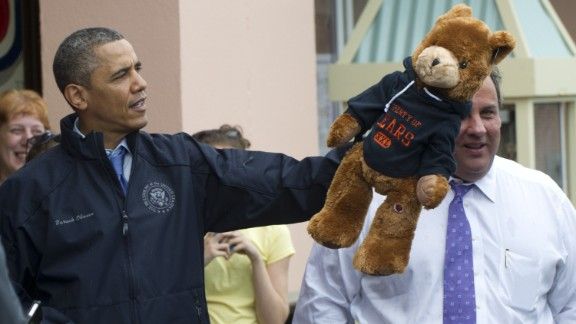 Obama holds up a stuffed bear after playing an arcade game along the Point Pleasand boardwalk.