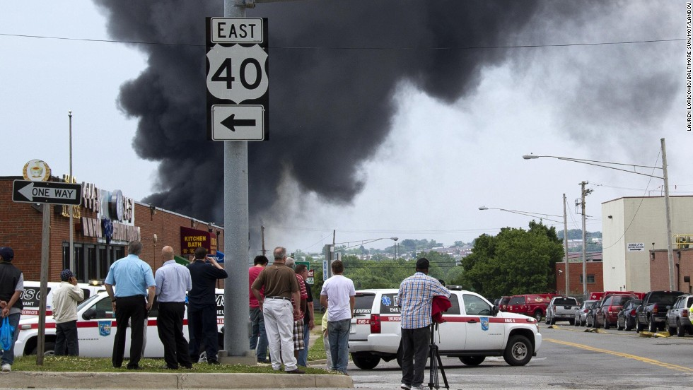 Onlookers stand at a distance as first responders investigate the possibility of toxic chemicals in the explosion.