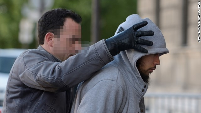 The suspected perpetrator (R) of the Sunday attack on a soldier is escorted to police headquarters in Paris on Wednesday.