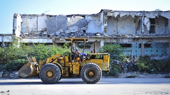 """""""If you go to Mogadishu the construction is very, very booming,"""" says Osman. Pictured, construction workers in November 2012."""