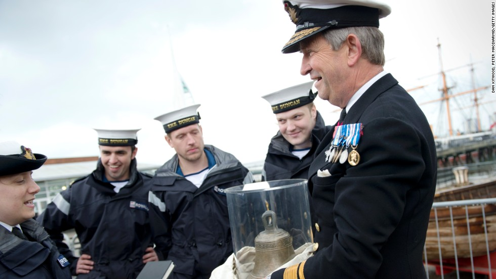 Rear Admiral John Lippiett, right, holds the original bell of the 16th century Tudor warship Mary Rose.