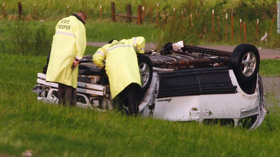 Oklahoma Highway Patrol Troopers inspect an overturned vehicle sitting alongside I-40 near El Reno on May 31.