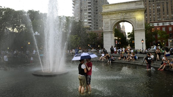 People cool off in a fountain at Washington Square Park in New York at dusk on Friday, May 31, as temperatures reached the 90s.