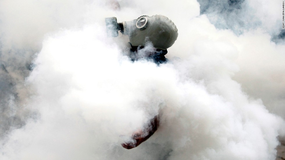 An activist wearing a gas mask is enveloped in a cloud of tear gas on May 31.